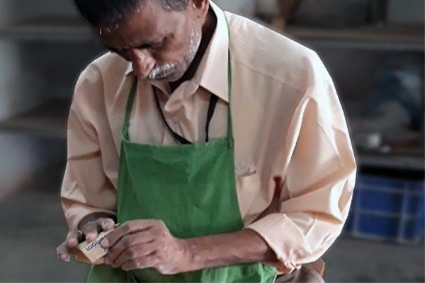elderly person doing wooden craft