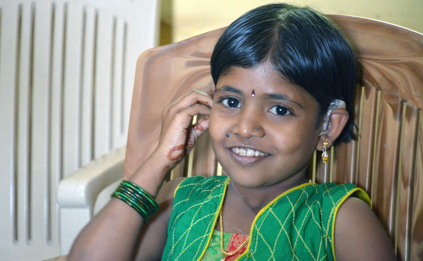 a girl with hearing impairment wearing her new hearing aid